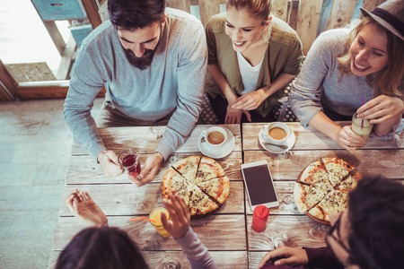 Young friends sharing pizza in a indoor cafe top view