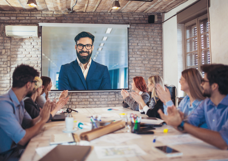 Business people looking at projector during video conference in office