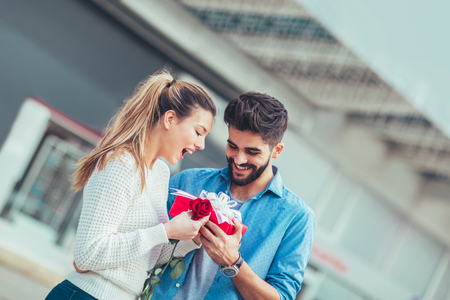 Romantic man giving flower and gift box to woman for Valentines day or anniversary