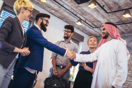 Cheerful group of business team welcoming arabian businessman