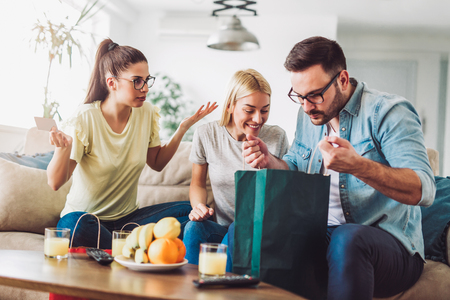 Two women and a man in a living room holding a credit card and shopping bags