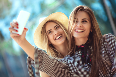 Two female friends taking a selfies, having fun outdoor Stock Photo