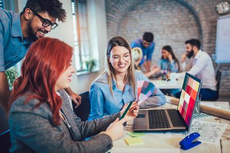 Gruppo di giovani imprenditori e designer guardando la tavolozza dei colori. Team di brainstorming nella sala riunioni con campioni di colore.