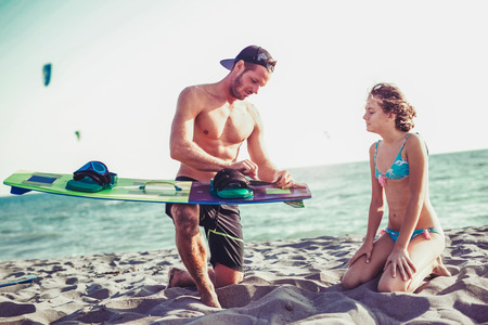 Man instructor teaches the young girl in kite surfing