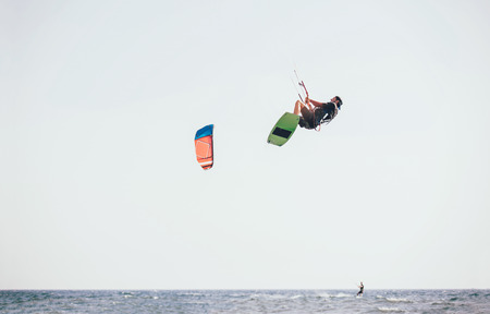 Kitesurfing Kiteboarding action photos man among waves quickly goes Stock Photo - 102279872