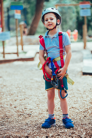 Little boy in adventure activity park with helmet and safety equipment