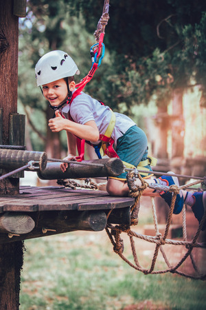Little boy climbing in adventure activity park with helmet and safety equipment showing thumbs up Stock Photo