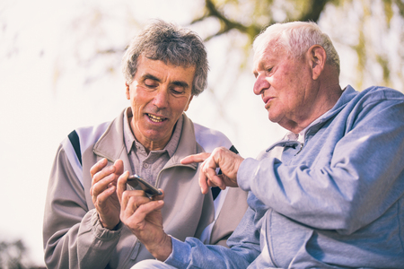 Two senior men using smart phone in the park