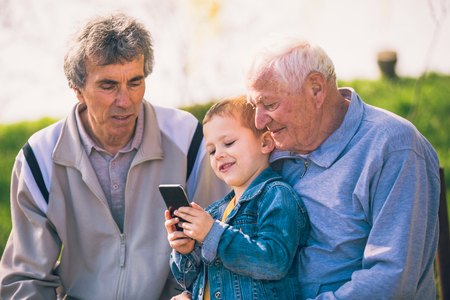 Two senior men and grandson using smart phone in the park Stock Photo