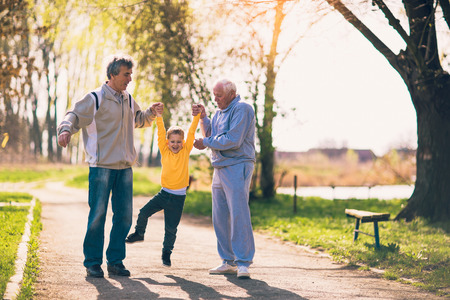Two grandfather walking with the grandson in the park Stock Photo