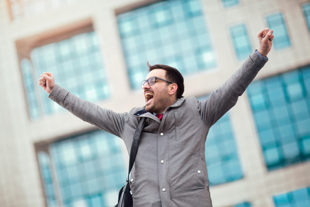 Businessman raising his arms outdoors - happy, success and achievement concepts Banco de Imagens