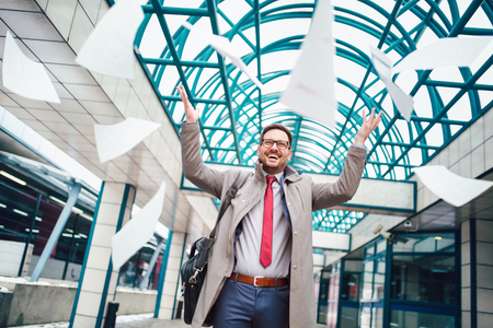 Business man celebrating by throwing papers in the air Stock Photo