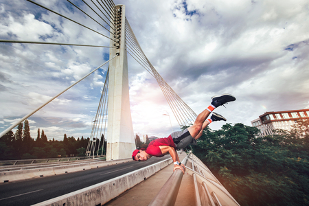 Full of energy.Young man extreme exercising on the bridge. Stock Photo