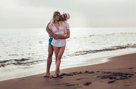Pareja romántica divirtiéndose en la playa. Pareja feliz corriendo en la playa al atardecer. Foto de archivo - 102719298