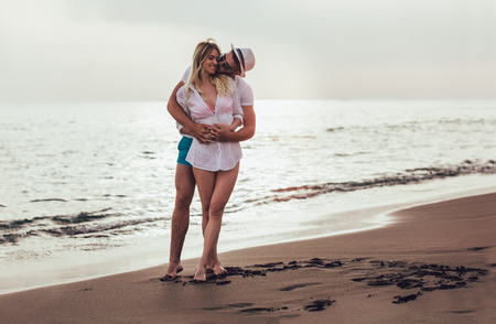 Romantisch paar met plezier op het strand. Gelukkige paar die op strand bij zonsondergang lopen. Stockfoto - 102719298