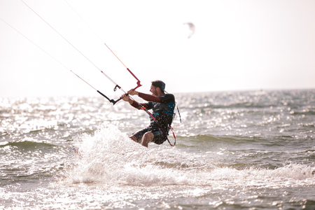 Kitesurfing Kiteboarding action photos man among waves quickly goes Stock Photo - 102720856