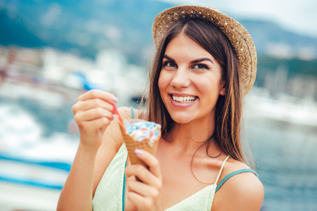 Woman eating ice cream outside on summer vacation in holiday beach resort.