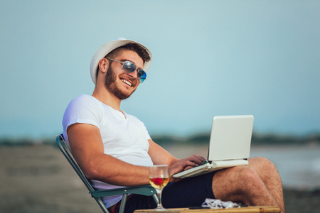 Man working with computer on the beach. Freelancer working Stock Photo