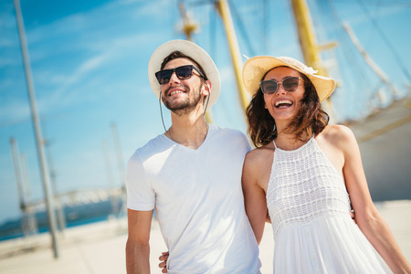 Happy young couple walking by the harbor of a touristic sea resort with sailboats on background