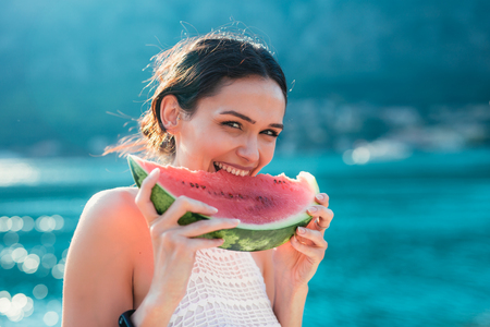 Attractive young woman on the beach eating watermelon