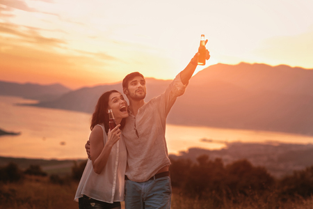 Portrait of young couple having good times in nature behind them is a beautiful sunset over Boka Bay Reklamní fotografie
