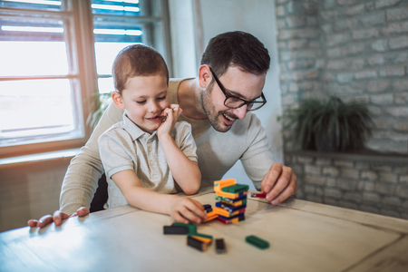 Father and adorable son playing with education game, family fun at home concept