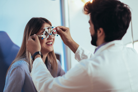 Optometrist checking patient eyesight and vision correction Stok Fotoğraf
