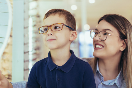 Mother with son choosing glasses in optics store.