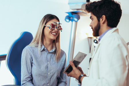 Optometrist checking patient eyesight and vision correction Stock Photo
