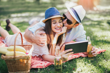 Couple lying on a picnic blanket in a park with a picnic basket filled with fruit, they are using digital tablet