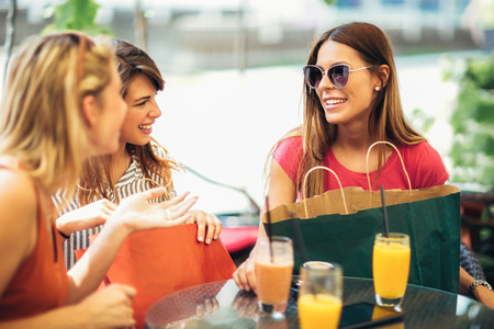 Three young women in a cafe after a shopping