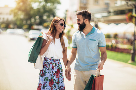 Beautiful couple enjoy shopping together, young couple holding shopping bags