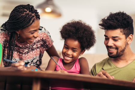 Mom and dad drawing with their daughter. African american family spending time together at home. Stock Photo