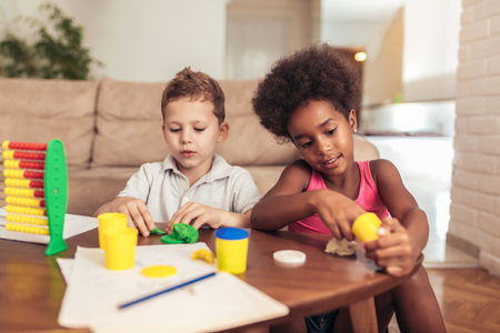 Cute little children mould from plasticine on table at home Stock Photo