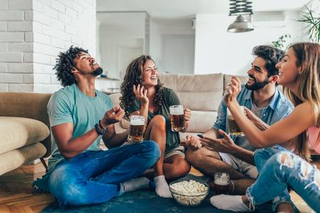Amigos comiendo palomitas de maíz y bebiendo jarra de cerveza en casa, divirtiéndose.