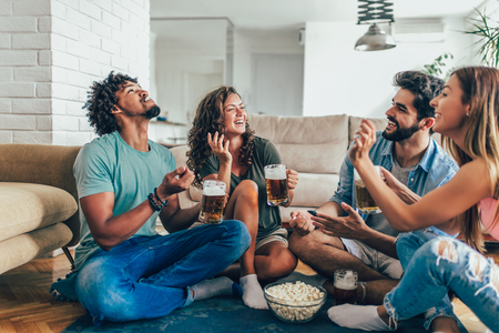 Friends eating popcorn and drinking beer mug at home, having fun. Фото со стока - 105384091