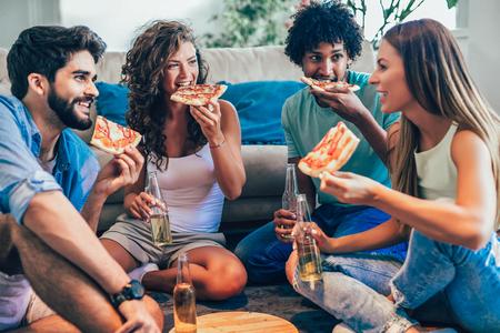 Grupo de jóvenes amigos comiendo pizza. Fiesta en casa.