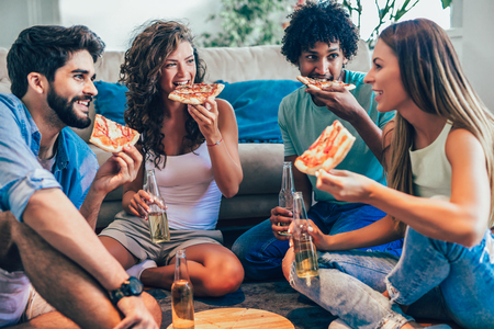Gruppo di giovani amici che mangiano pizza Festa in casa.