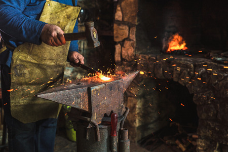 Blacksmith manually forging the molten metal on the anvil in smithy with spark fireworks, close up