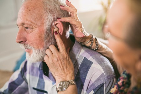 Older man and woman or pensioners with a hearing problem
