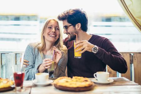 Lächelndes Paar, das in Pizza genießt, Spaß zusammen hat.