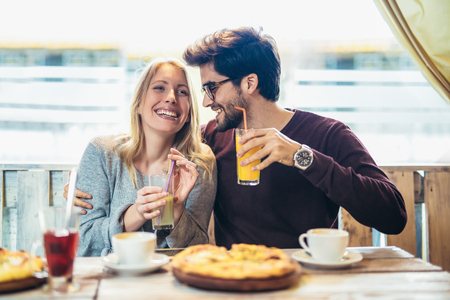 Smiling couple enjoying in pizza, having fun together.
