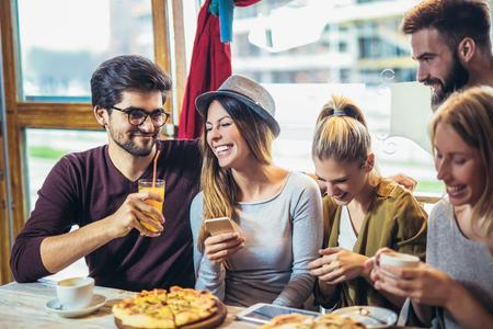 Jóvenes amigos compartiendo pizza en un café interior Foto de archivo