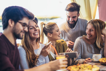Jeunes amis partageant une pizza dans un café intérieur