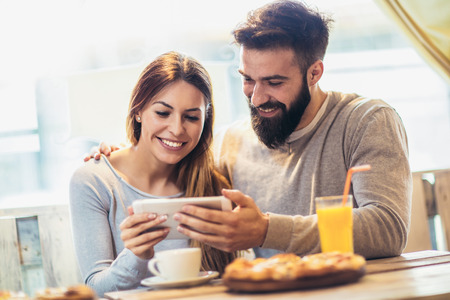 Smiling couple enjoying in pizza, having fun together and using tablet pc.