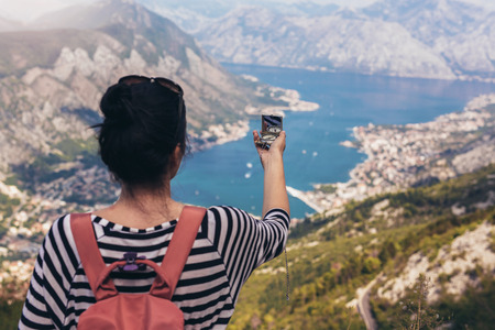 Tourist hold compass on trip, lifestyle concept adventure, traveler with backpack on background mountain and blue sea landscape horizon. View of the Bay of Kotor from the mountains Lovcen. 写真素材