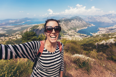 Smiling young woman takes a selfie on background mountain and blue sea landscape horizon. View of the Bay of Kotor from the mountains Lovcen.