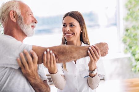Hombre con ajuste de brazo quiropráctico. Fisioterapia, rehabilitación de lesiones deportivas. Ejercicios de hombre mayor en el centro de quiropráctica.