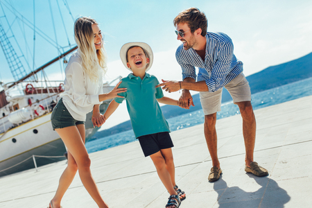 Happy family having fun, enjoying the summer time by the sea. Stock Photo