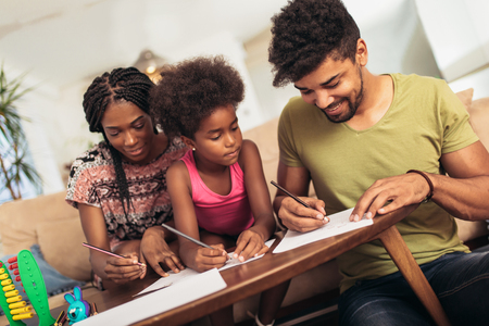 Mom and dad drawing with their daughter. African american family spending time together at home. Imagens